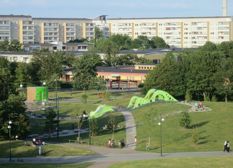 Foto av stadsdelen Holma, sedd från Kroksbäcksparken, med höga hus i bakgrunden och en park i förgrunden. Parken består av lekplatser, träd, buskar, gräsmatta. Bild: Jorchr, CC BY-SA 3.0, Wikipedia.