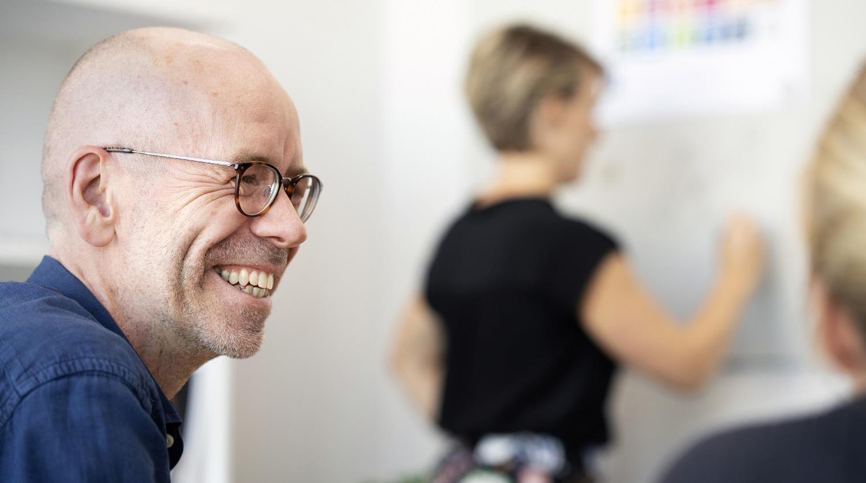 Person som skrattar på ett möte. Foto.