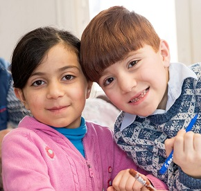 Två glada barn som tittar in i kameran