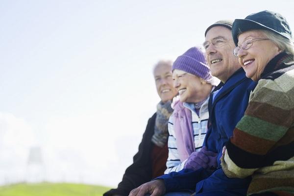 Fyra ädre personer i rad, leende i solskenet