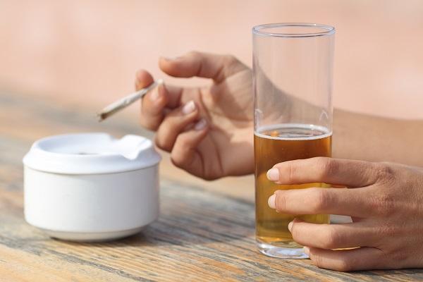 Händer som håller i ett ölglas och en cigarett