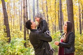 Pappa som håller i sitt barn och mamma som tittar på