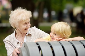 Äldre dam med litet barn i en park
