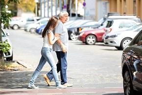 Yngre kvinna hjälper äldre man över vägen