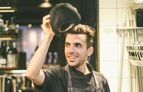 Man som står i ett kök med förkläde på och tar på sig en keps