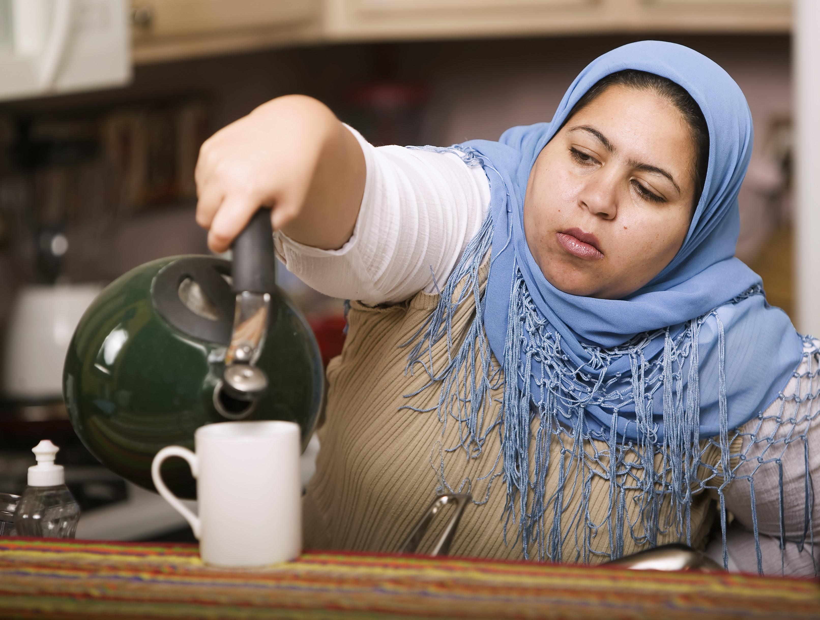 Muslimsk kvinna med duk på huvudet häller te ur tekanna