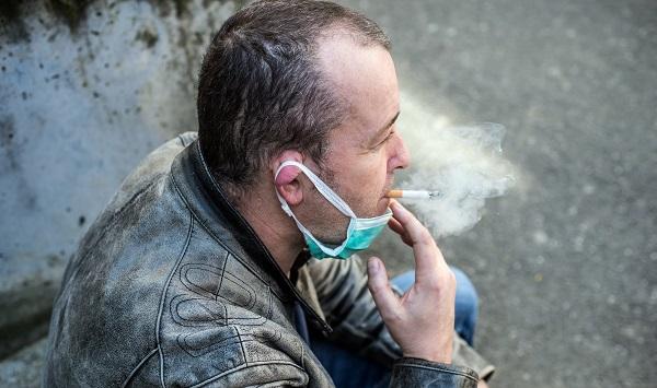 Man som röker cigarett med munskydd vid hakan