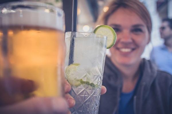 Två människor som skålar med en öloch en drink