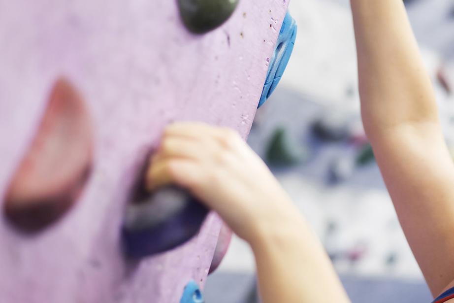 Händer som klättrar på en klättervägg inomhus