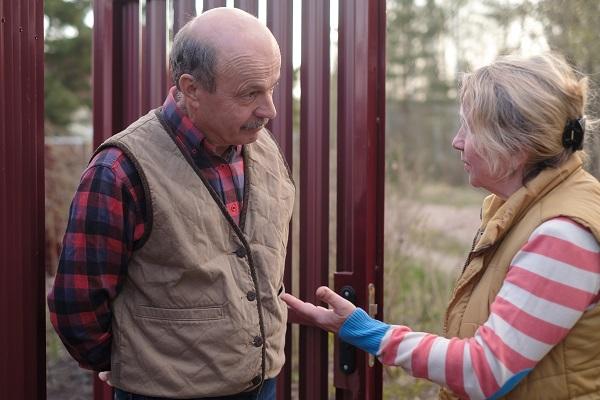 Äldre man och kvinna står utomhus och diskuterar med varandra