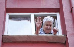 Äldre kvinna tittar ut från ett fönster och vinkar