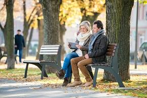 Medelålders man och kvinna på en parkbänk, tittar på en surfplatta