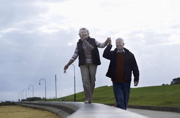 Äldre kvinna går på en spång och äldre man håller henne i handen