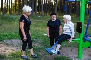 Tre äldre kvinnor på ett utegym