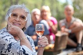 Äldre kvinna höjer ett vinglas, med en grupp äldre människor i bakgrunden som sittre utomhus på picknick