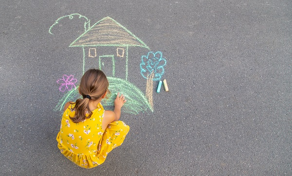 Liten flicka ritar hus med gård på asfalten med gatukritor