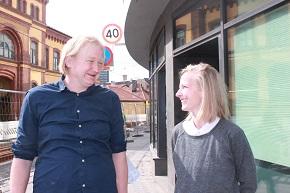 Man och kvinna som diskuterar med och ler mot varandra på en gata