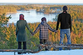 En man, barn och kvinna som står på rad och blickar ut mot sjö och skog, håller varandra i handen
