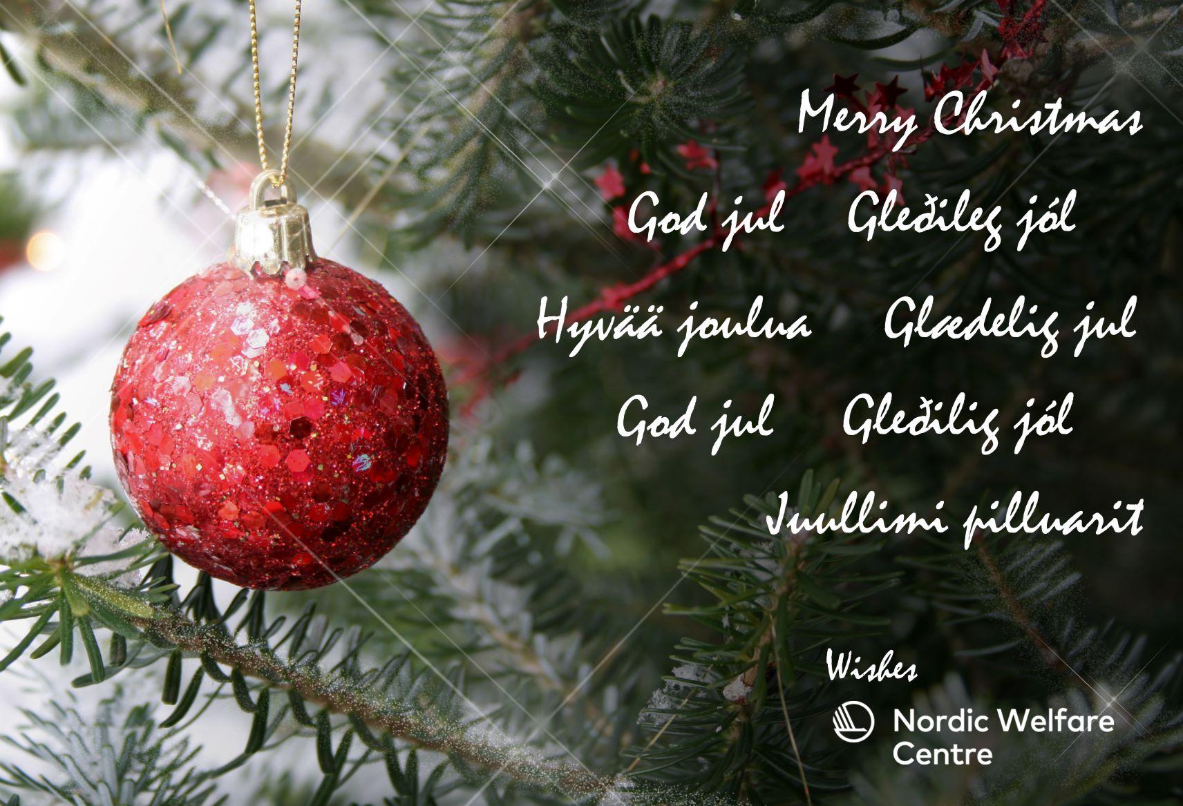 Julgran med röd julgranskula i. God jul skrivet på nordiska språk