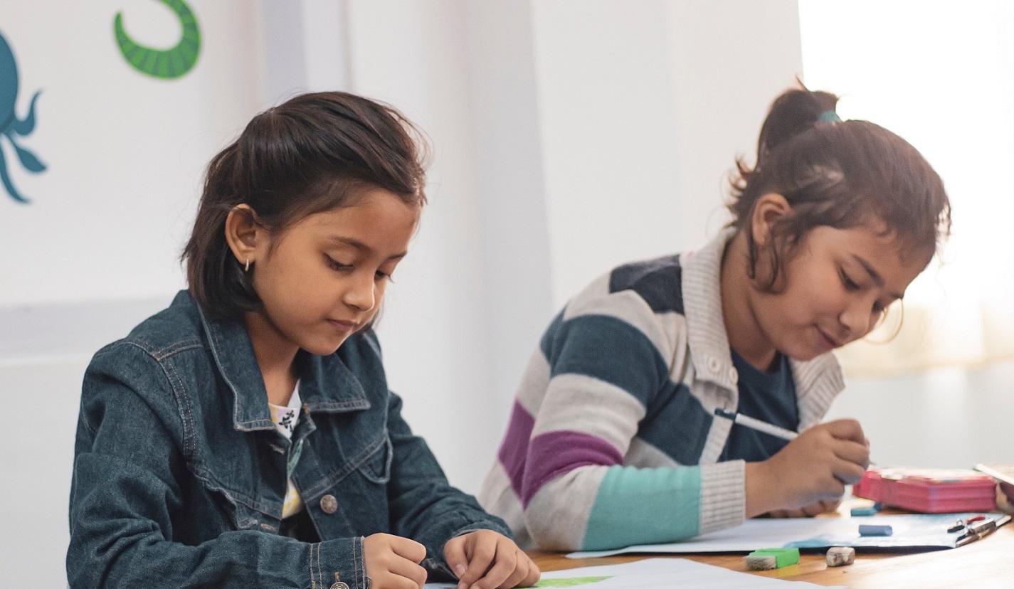 Två flickor i 8-9 årsåldern sitter i skolbänken
