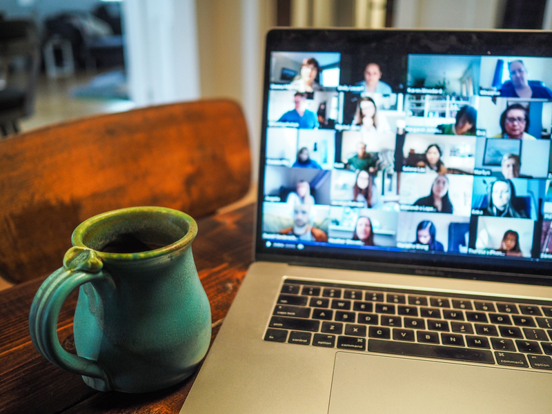 Laptop med videomöte, vid sidan står ett grönt krus