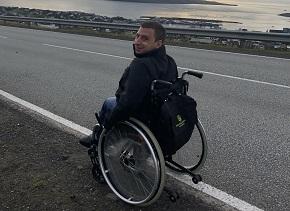 Man i rullstol utomhus vid en väg tittar över axeln mot kameran