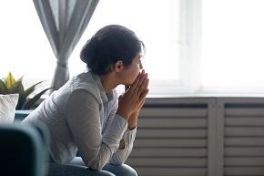 Fundersam kvinna med händerna vid ansiktet tittar utgenom fönster.
