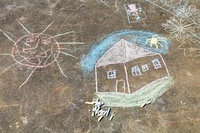 Hus ritat med gatukritor på asfalt