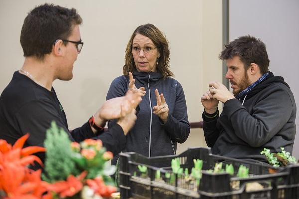 Tre människor som diskuterar med varandra med teckenspråk
