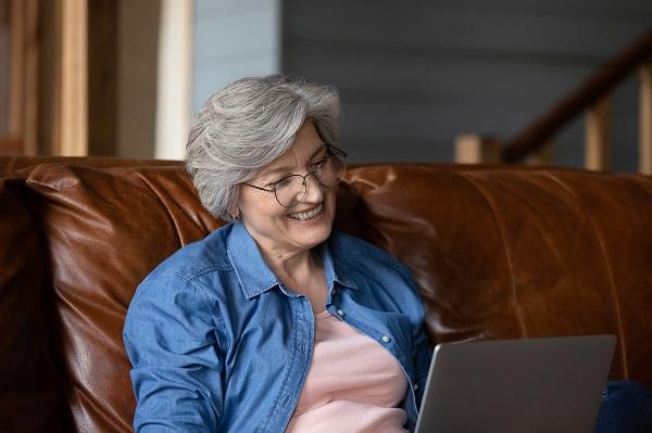 Äldte kvinna sitter leende framför datorskärm
