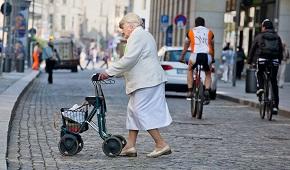 Äldre kvinna går med rollator över vägen i stadsmiljö