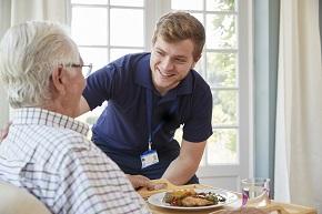 Yngre manlig vårdare tar hand om en äldre man som sitter och äter
