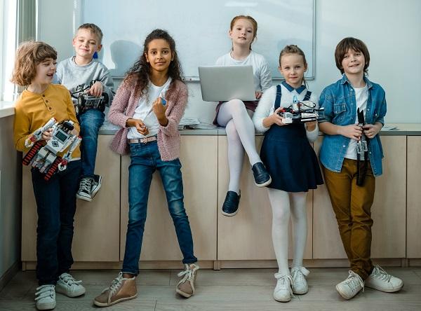 Barn i lågstadieåldern på rad, poserar i ett klassrum och tittar mot kameran