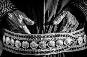 Detaljbild av man som sticker ner händerna i sitt bälte på en traditionell samedräkt