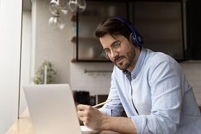 Man med hörlurar tittar på en datorskärm och tar anteckningar