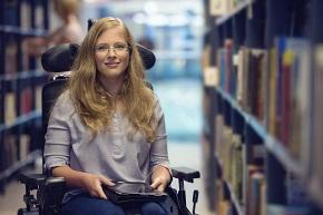 Kvinna i rullstol omringad av bokhyllor på ett bibliotek