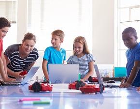 Skolbarn i klassrum med sin lärare, de programmerar robotar med hjälp av datorer