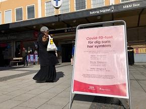 Mörkhyad kvinna utomhus vid en skylt där det informeras om covidtest