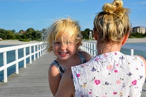 Litet leende barn i famnen på en kvinna på en brygga i solskenet