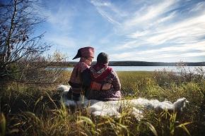 Ett äldre par iklädda traditionella samedräkter sitter utomhus och tittar mot vatten, mannen håller om kvinnan.