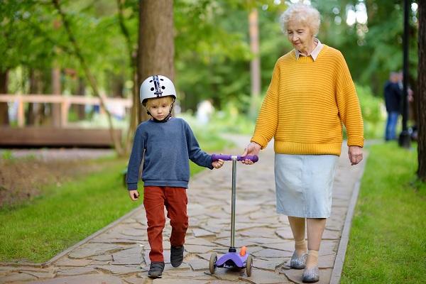 Äldre kvinna ute och går med ett litet barn, mellan sig leder de barnets sparkcyel