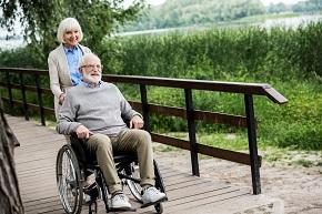En äldre kvinna som står bakom en rullstol med en äldre man sittandes i den.