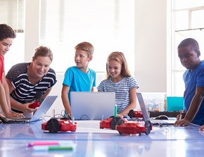 Children and their teacher, programming robots with the help of computers