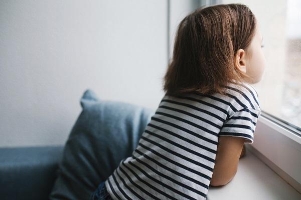 Litet barn tittar ut genom fönstret