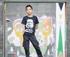 Ung pojke står vid en skatepark med graffitti i bakgrunden