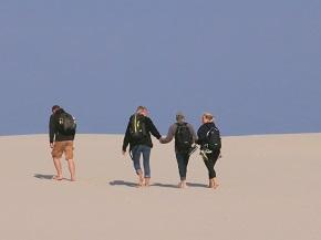 Fyra människor som är ute och går på sanddyner i solsken