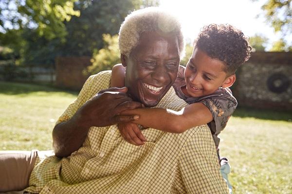 Liten pojke kramar äldre man, utomhus på en gräsmatta