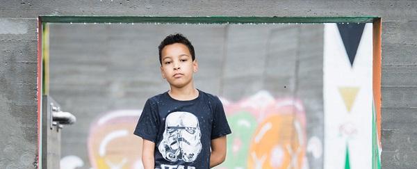 Pojke står framför en graffitivägg.