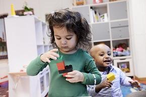 Två barn leker med klossar.