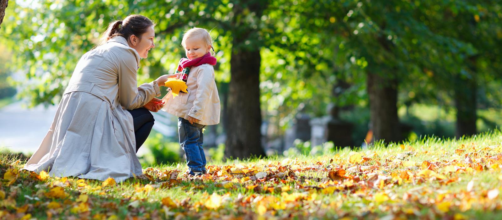 Kvinna lyfter upp ett gulnat löv till sitt barn ute i en park med höstlöv på marken.